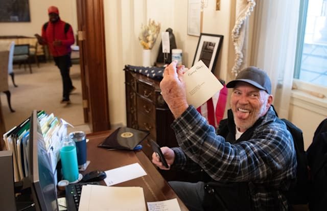 (FILES) Richard Barnett, a supporter of US President Donald Trump, holds a piece of mail as he sits inside the office of US Speaker of the House Nancy Pelosi after protestors breached the US Capitol in the US Capitol in Washington, DC, January 6, 2021. - Demonstrators breeched security and entered the Capitol as Congress debated the 2020 presidential election Electoral Vote Certification. (Photo by SAUL LOEB / AFP) (Photo by SAUL LOEB/AFP via Getty Images)