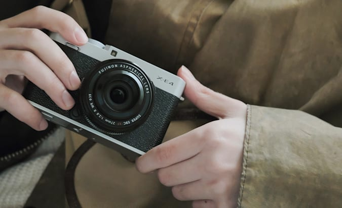 A Fujifilm X-E4 held in someone's hands close to their chest.