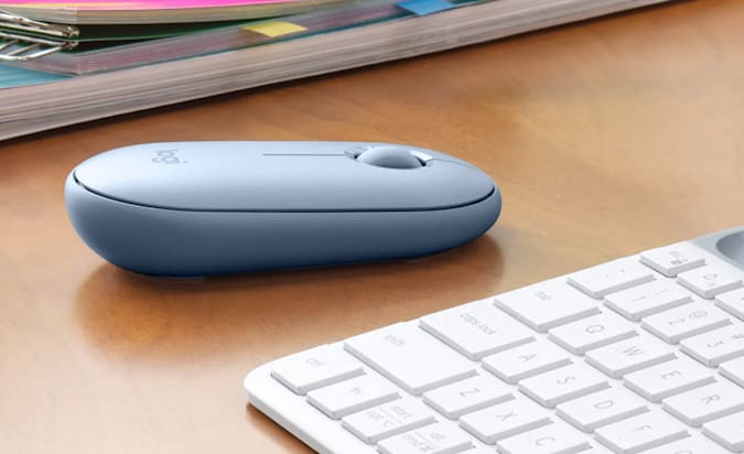 The Logitech Pebble mouse in light blue sitting on a desk next to a keyboard.