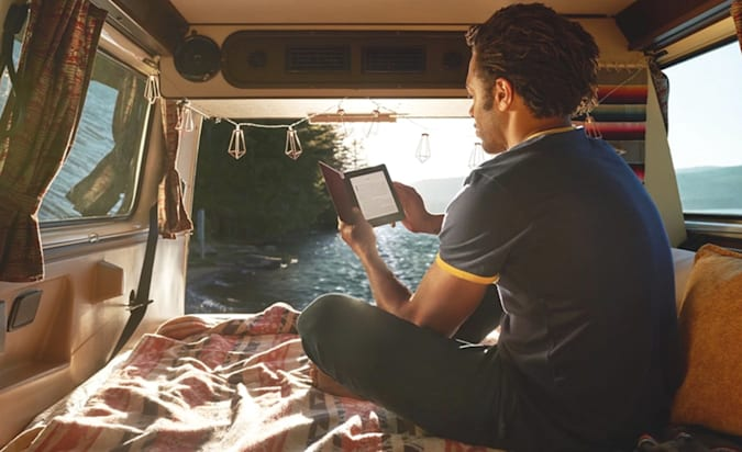 A man in the back of a van reads on a Kindle Paperwhite e-reader.