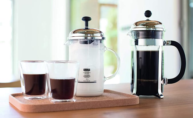 A Bodum Chambord french press on a table with milk and two coffee cups.