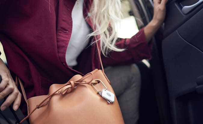 A woman's bag on the passenger seat of a car has a Tile Pro hooked onto its strap.