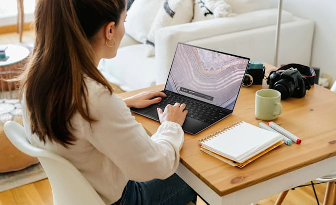 A woman works on a Dell XPS 13 laptop on her home desk.