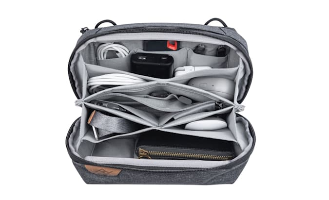 A Peak Design Tech Pouch opened up showing its pockets filled with products.