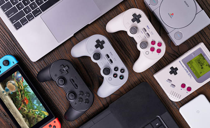 An overview photo of the 8BitDo Pro 2 gaming controller lined up neatly next to a variety of compatible game platforms.