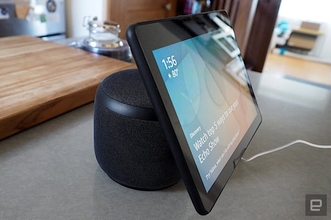 Amazon Echo Show 10 with its screen on, sitting on a counter in front of a wooden cutting board.