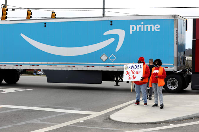 People hold a banner at the Amazon facility as members of a congressional delegation arrive to show their support for workers who will vote on whether to unionize, in Bessemer, Alabama, U.S. March 5, 2021.  REUTERS/Dustin Chambers?