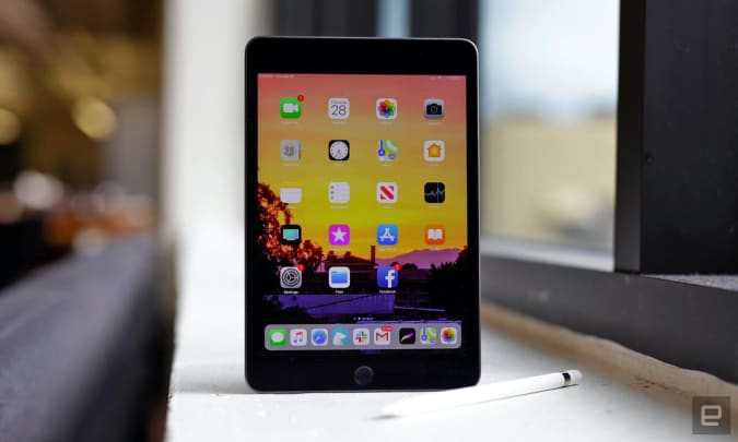 The Apple iPad mini and stylus sit on an office window sill.