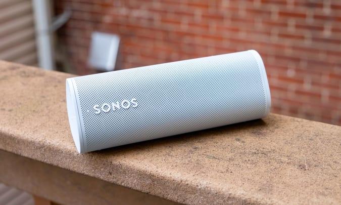 A white Sonos Roam speaker sitting on an outdoor ledge.