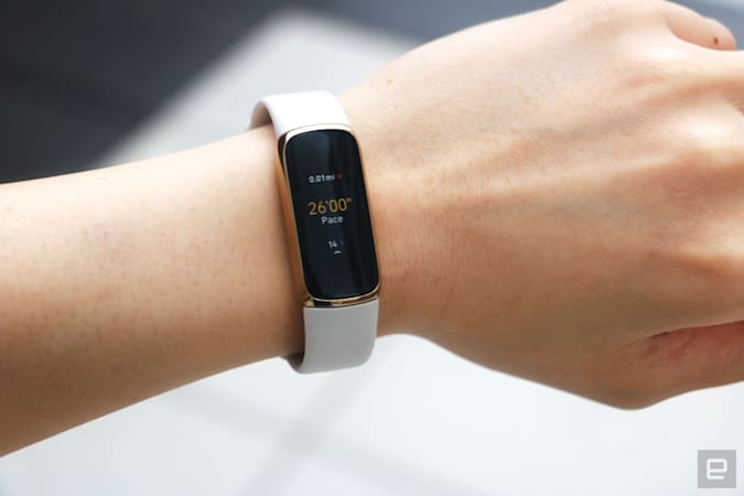 The Fitbit Luxe with a light pink silicone band on a wrist against a concrete gray background. The screen shows a run being tracked with a pace of 26:00 and 0.01 miles traveled.
