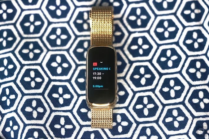 Front view of the Fitbit Luxe with a gold mesh bracelet on a patterned blue and white background. Its screen shows a calendar notification for an event from 5:30pm to 7pm.