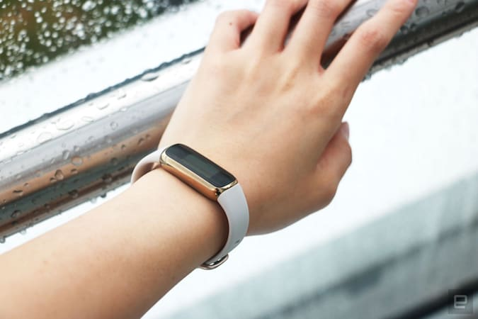 The Fitbit Luxe with a light pink silicone band on a wrist leaning on a wet railing. The screen is off.