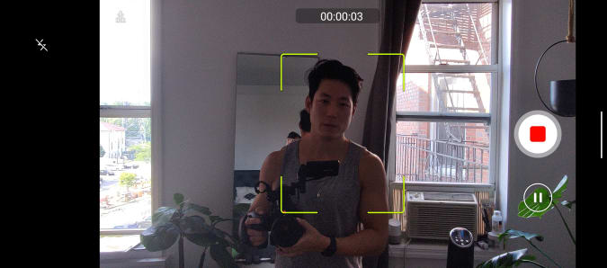 A screenshot of the camera app in the Smartphone for Snapdragon Insiders, demonstrating an Auto Tracking video recording mode. There is a yellow square surrounding a man and Stop and Pause buttons on the right..