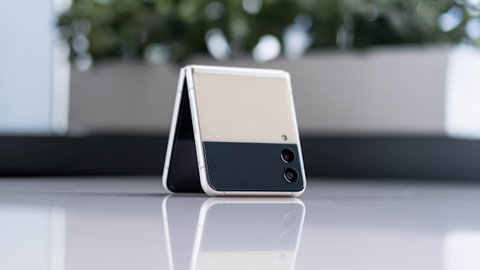 The Samsung Galaxy Z Flip 3 folded and propped up in tent mode on a table.