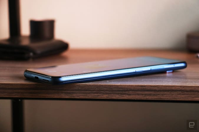 Side view of the Smartphone for Snapdragon Insiders laid on a wooden surface, showing its power and volume buttons on the right edge.