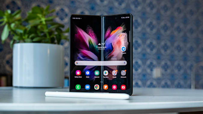 A Samsung Galaxy Z Fold 3 on a table with an S Pen Pro in front of it.
