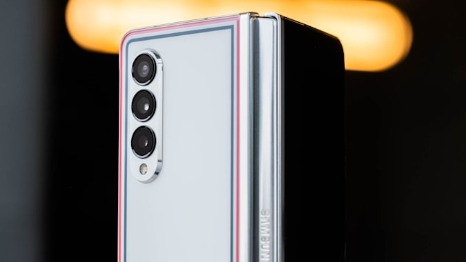 The Thom Browne edition of the Samsung Galaxy Z Fold half opened and with its back facing the camera.