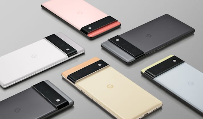 Six Google Pixel 6 and Pixel 6 Pro devices laying on a grey surface at various angles, perpendicular to each other.