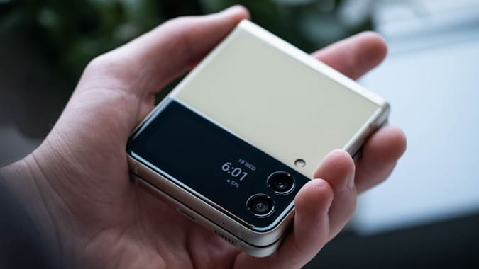 A hand holding the closed Samsung Galaxy Z Flip 3 with its Cover Display facing the camera.