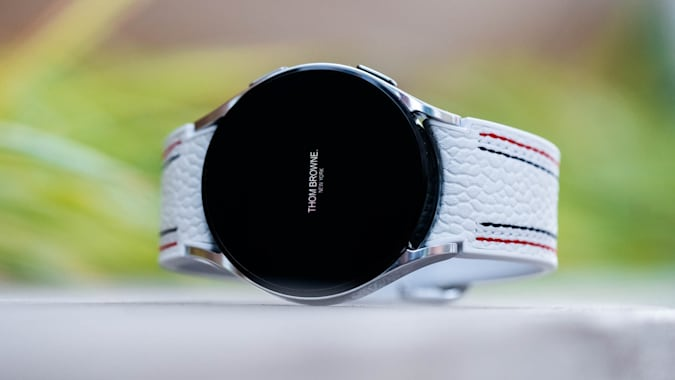 A Thom Browne edition of the Samsung Galaxy Watch 4 laying on its side with greenery in the background.
