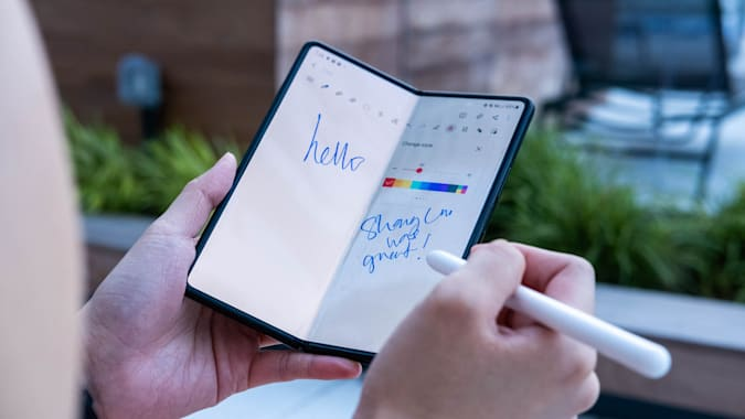 A person using the S Pen Pro to draw on the Samsung Galaxy Z Fold 3. They are holding the phone, half-folded, in their left hand with an S Pen Pro in their right. On the screen, they've scrawled