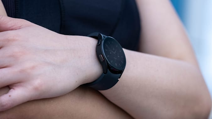 Side view of a black Samsung Galaxy Watch 4 on a person who has their arms folded across their chest.