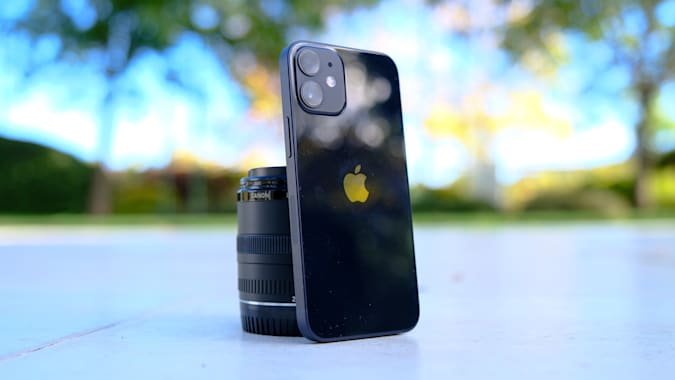 Apple iPhone 12 mini against a camera lens