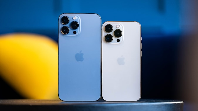 A blue iPhone 13 Pro Mac and a gold iPhone 13 Pro next to each other on a table with their rear cameras facing us.