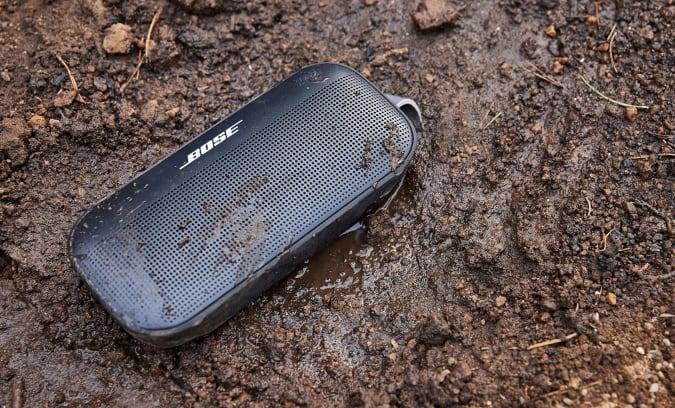 A Bose SoundLink Flex portable Bluetooth speaker in some mud.