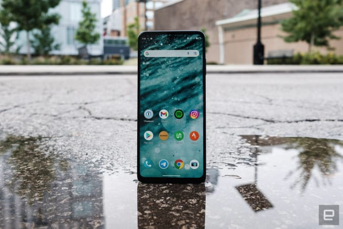 The Motorola Moto Edge photographed in the street standing up on the edge of a puddle with its reflection visible in the foreground.