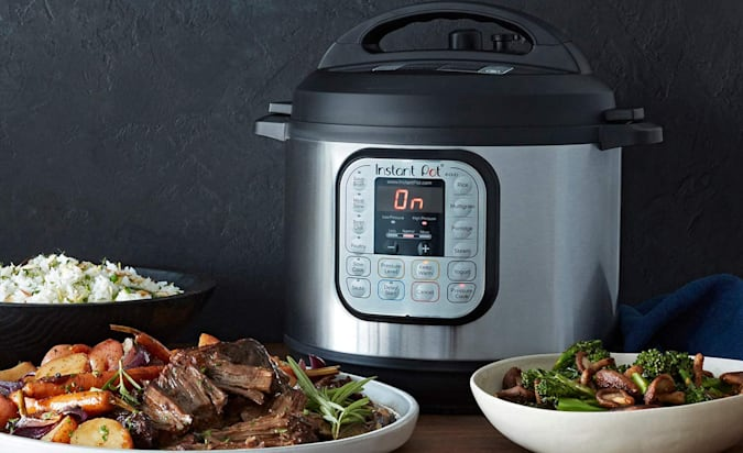An Instant Pot Duo 6 on a table next to plates of food.
