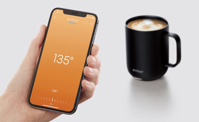 The ember smart hot liquid mug seen in a grey void next to a hand holding a smartphone with temperature controls on the screen.