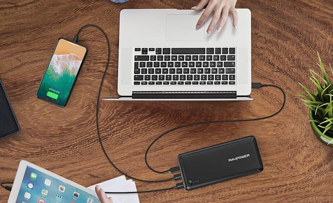 A RAVPower charger photographed from above next to a laptop, phone and tablet, all being charged.