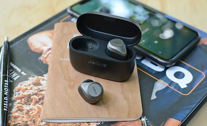 The Jabra Elite 85t and charging case sitting on top of magazines on a countertop.
