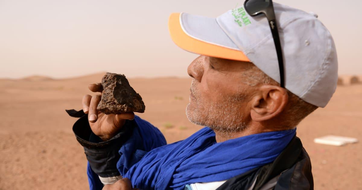 Un chasseur de météorite dans le sud du Maroc examine une roche près de l'oasis de M'hamid El Ghizlane, le 25 mars 2018. / Ph. AFP