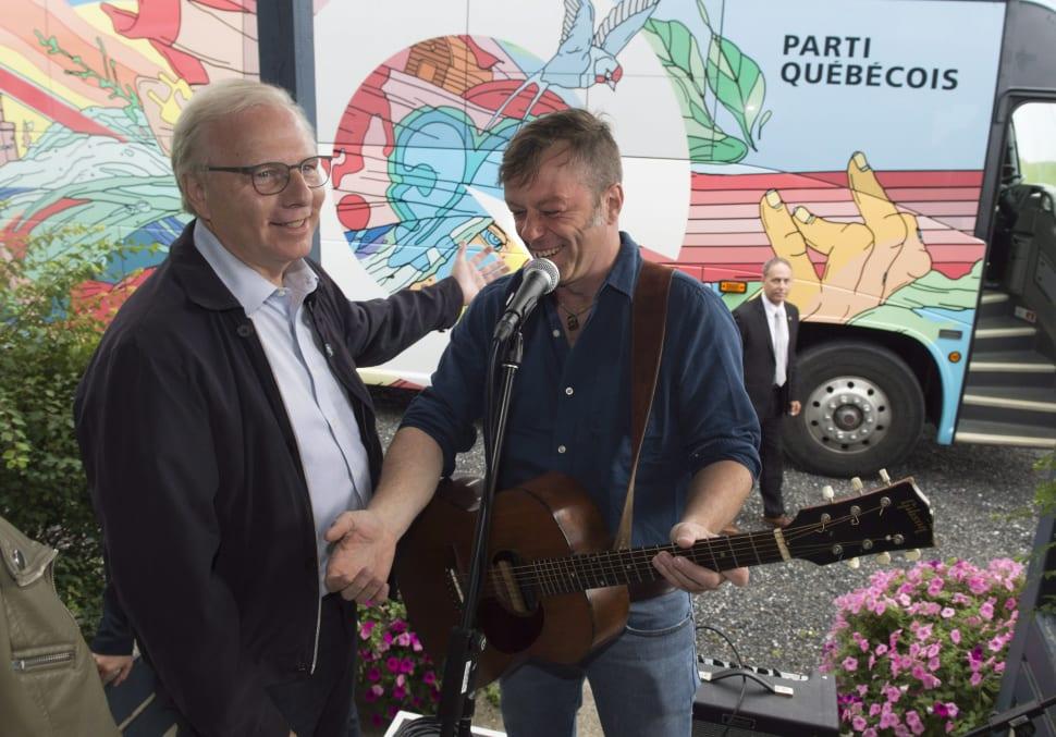 Jean-François Lisée en compagnie du chanteur Daniel Boucher devant l'autobus psychédélique du