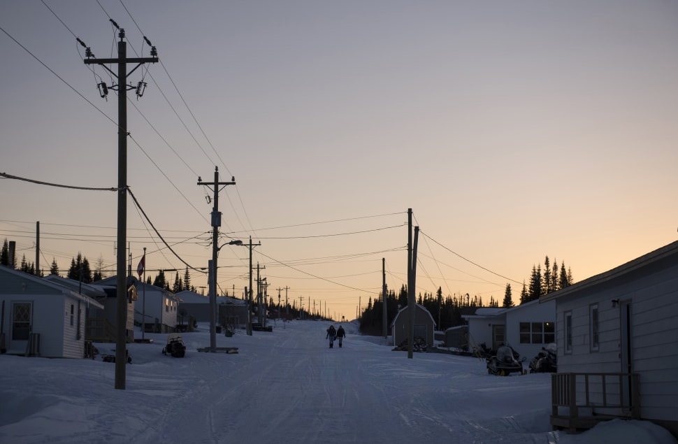 Girls walk through one of the main roads in Rigolet as the sun sets on the remote village on Labrador...