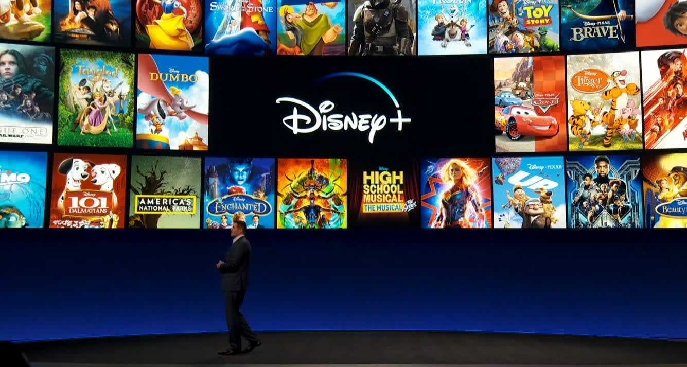 Man standing in front of a screen with Disney+ logo and Disney movie titles
