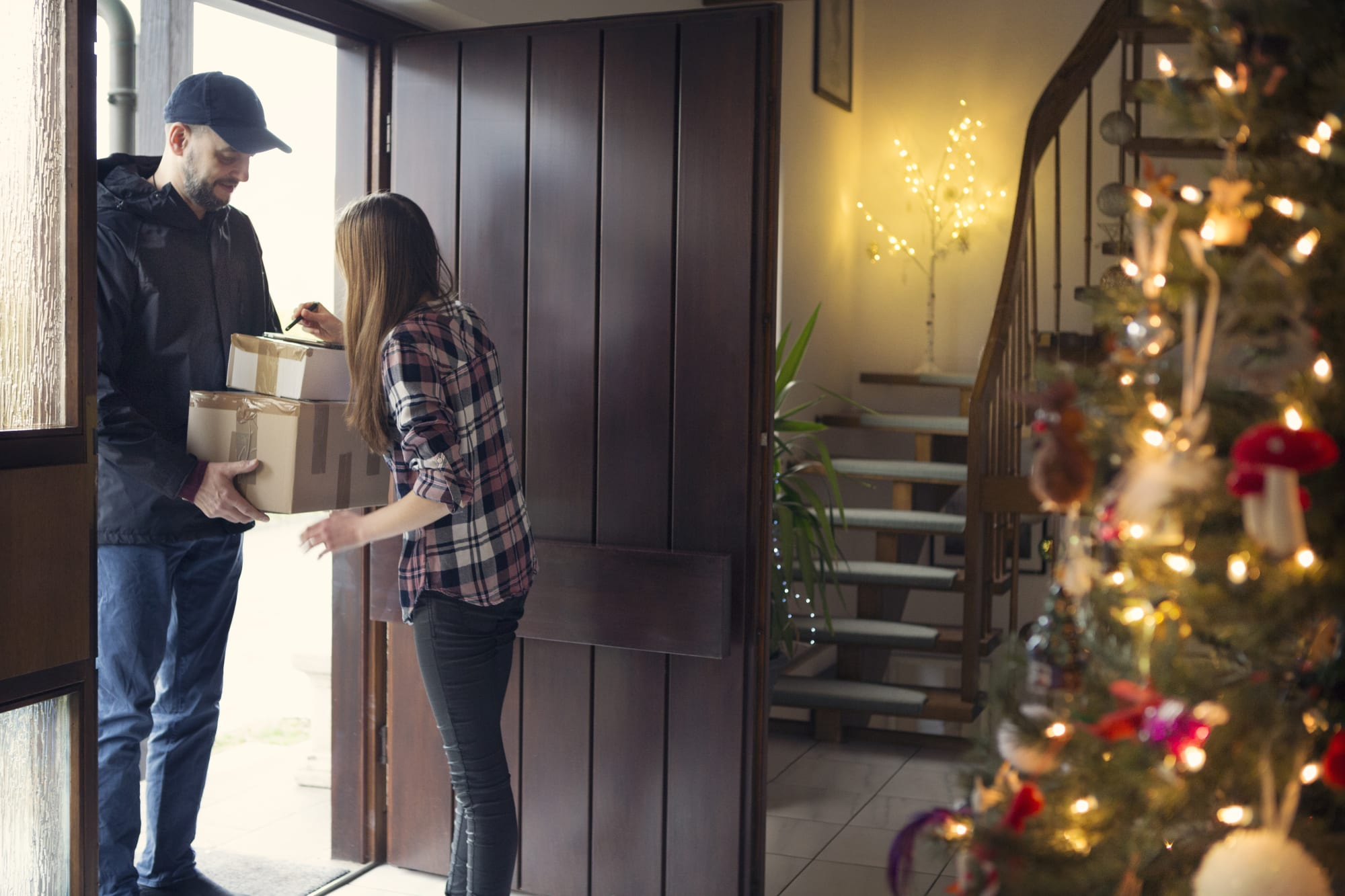 Teenager receiving Christmas packages delivered by postman