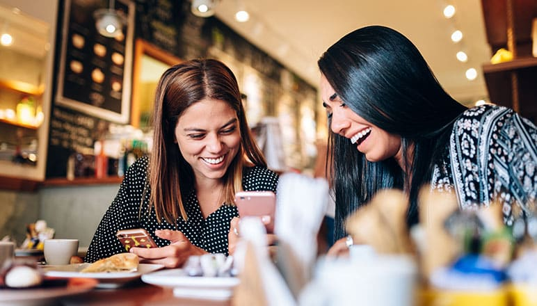 Two women smiling watching video on mobile