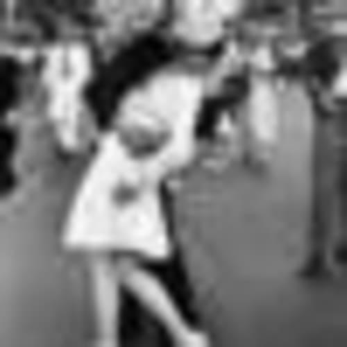 A jubilant American sailor clutching a white-uniformed nurse