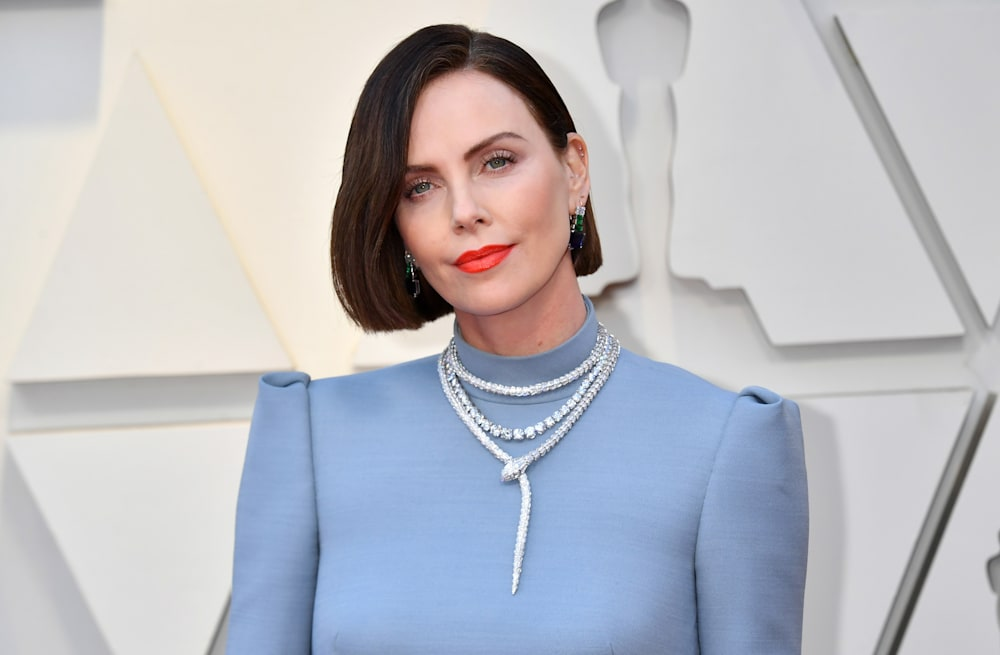 4b2063591e Slideshow preview image. 9 PHOTOS. Charlize Theron debuts brunette hair at  2019 Oscars