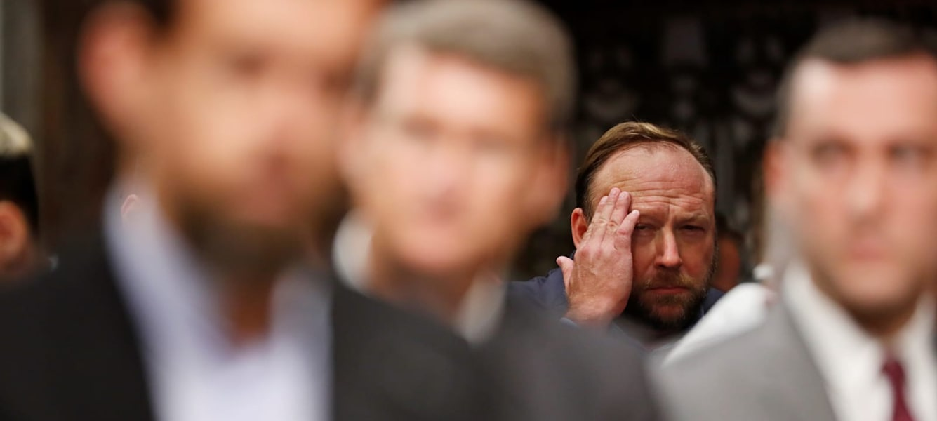 Alex Jones of Infowars rubs his brow as he sits in the audience listening to Twitter CEO Jack Dorsey (L) testify before a Senate Intelligence Committee hearing on foreign influence operations on social media platforms on Capitol Hill in Washington, U.S., September 5, 2018.