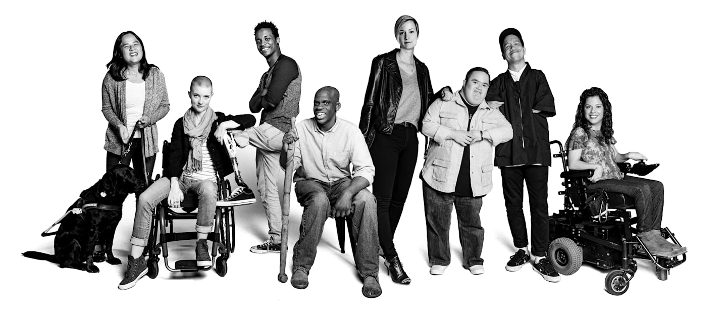 Black and white picture of diverse group of people, some in wheelchairs, one with a guide dog, one with a cane, smiling and proud.