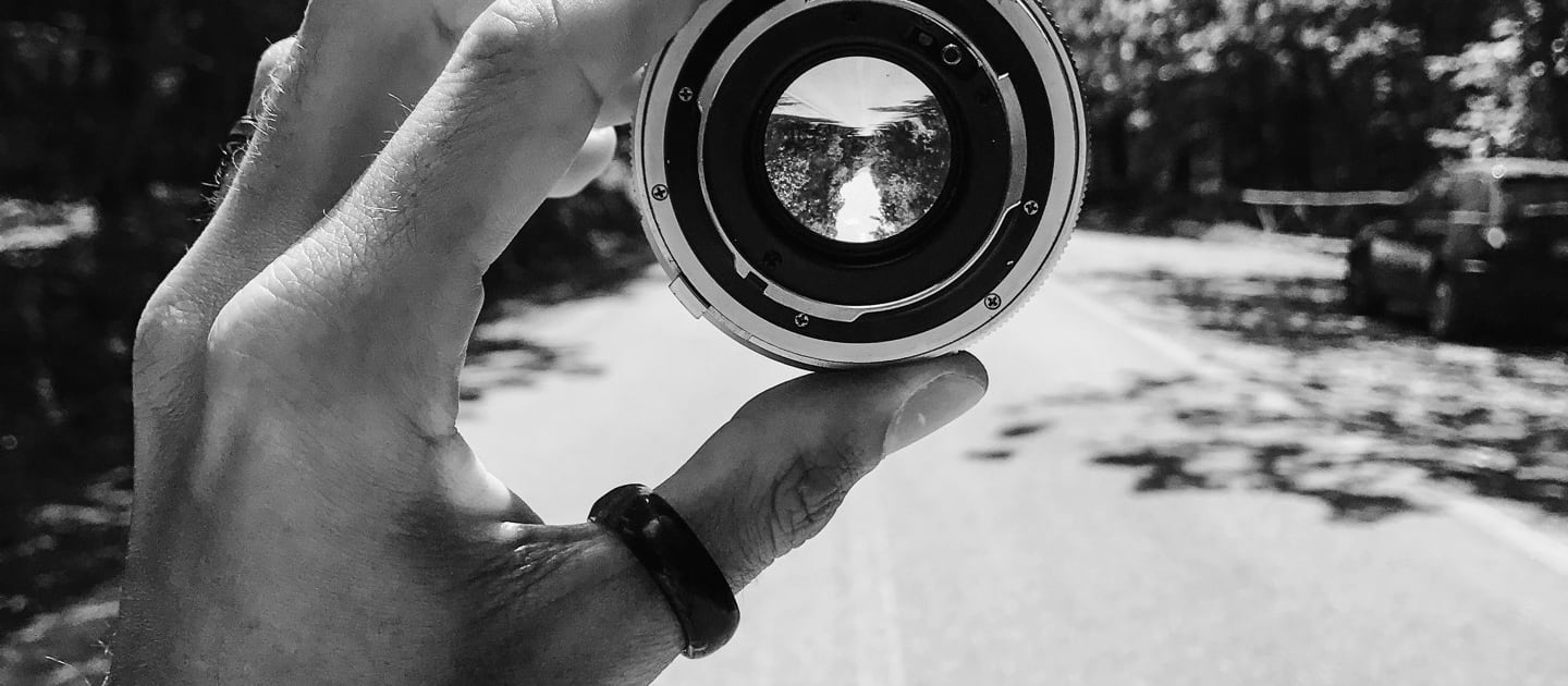 Hands holding a magnifying lens.