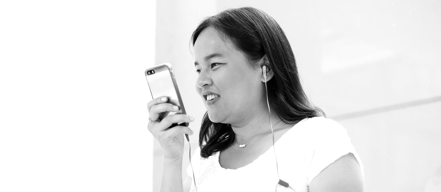 A woman wearing headphones uses a mobile phone.