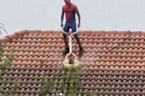 Undaunted by Pouring Rain, Spiderman Just Needs to Get This Roof Clean