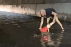 Woman Helps to Clear Clogged Drains During Flash Flooding in Brooklyn
