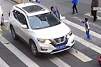 Furious child kicks out at car that knocked over his mother at zebra crossing in China