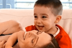 Mom lays on toddler's lap and his reaction is priceless